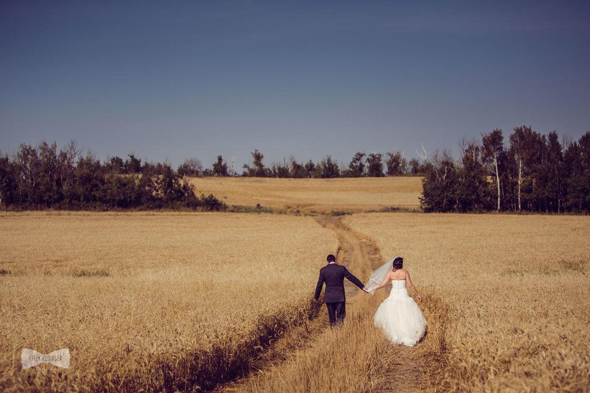 Жених и невеста бегут по полю пшеницы