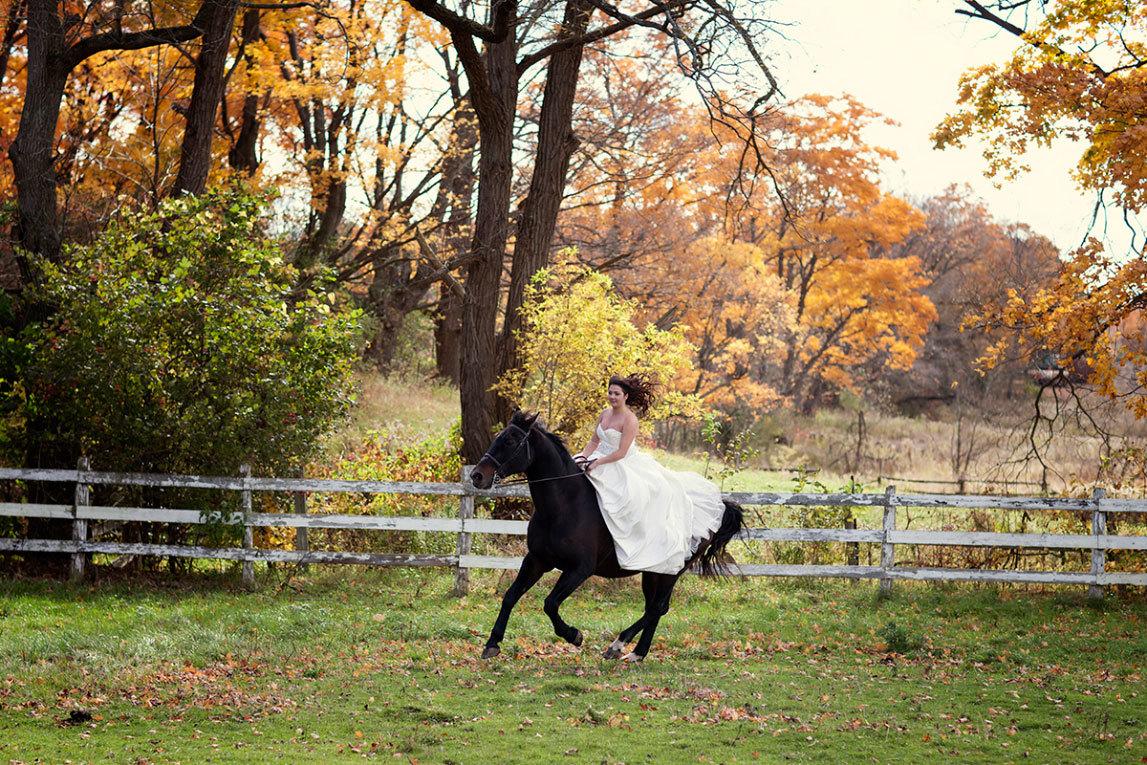 в свадебном платье верхом на лошади